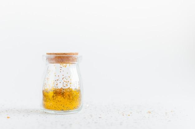 Глиттер боке фон. глиттер золотистого цвета и конфетти в стеклянной бутылке. основная тенденция концепции. натуральное и аутентичное настроение.