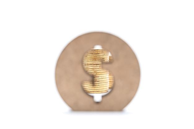 글로벌 비즈니스 및 돈 개념입니다. 흰색 바탕에 나무 미국 달러 기호 뒤에 금화 스택의 근접 촬영.