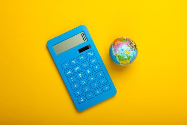 Глобальный бизнес, экономика. глобус с калькулятором на желтом фоне. вид сверху.