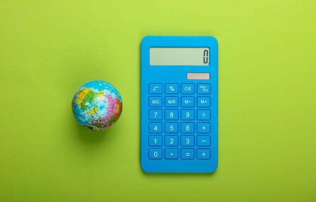 Глобальный бизнес, экономика. глобус с калькулятором на зеленом фоне. вид сверху.