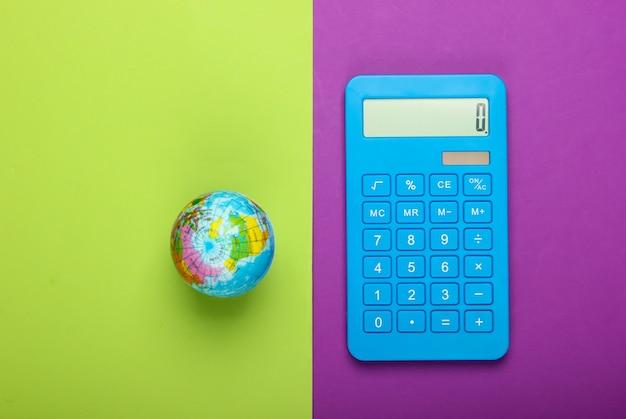 Глобальный бизнес, экономика. глобус с калькулятором на зеленом фиолетовом фоне. вид сверху.