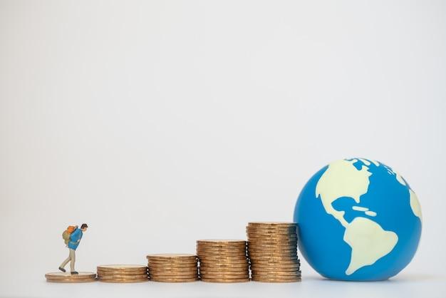グローバル出張と節約の概念。ミニワールドボールと金貨のスタックの上を歩くバックパックと旅行者のミニチュア