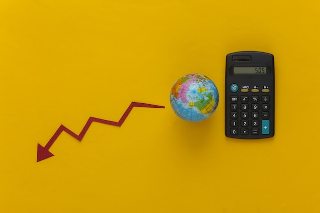 Global crisis theme. calculator with a globe, falling arrow tending down on a yellow