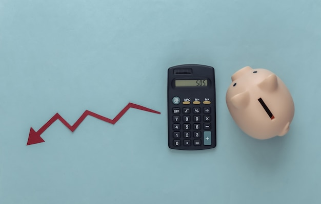 Тема глобального кризиса. калькулятор с копилкой, падающая стрелка, стремящаяся вниз на синем