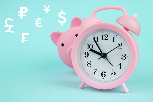 Global currency exchange concept pink piggy bank in the shape of pig with digital hologram hologram world currencies on blue background. save you time concept.