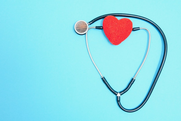 Global healthcare concept.stylish doctor with heart on blue background.close-up of red heart and stethoscope on a blue background. listen to the heart with statoscope.