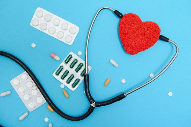 글로벌 의료 개념입니다. 파란색 배경에 마음으로 세련 된 의사입니다. 붉은 마음과 파란색 배경에 청진 기의 클로즈업입니다. statoscope로 심장의 소리를 듣습니다.