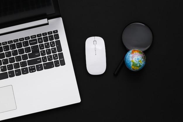 グローバルネットワーク。黒の背景にpcマウスとグローブを搭載したラップトップ。上面図。フラットレイ