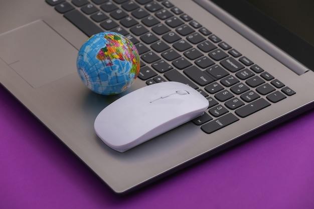 Глобальная сеть. ноутбук с компьютерной мышью и глобусом на фиолетовом фоне. интернет работа, покупки.