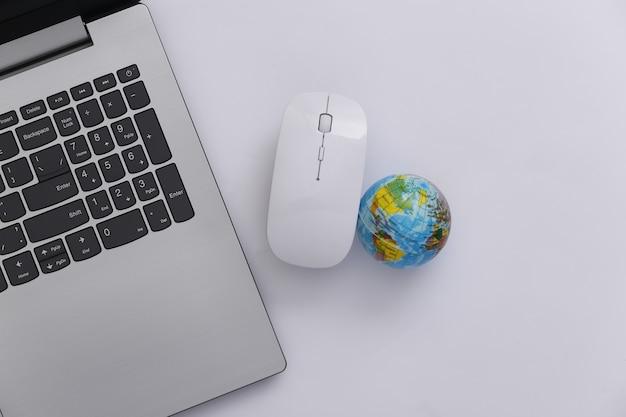 Глобальная сеть. ноутбук с компьютерной мышью и глобусом на белом фоне. интернет-бизнес. вид сверху. плоская планировка