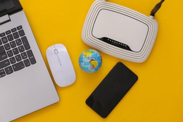 Глобальная сеть. ноутбук с wi-fi роутером, смартфоном, глобусом на желтом фоне. студийный снимок. вид сверху. плоская планировка