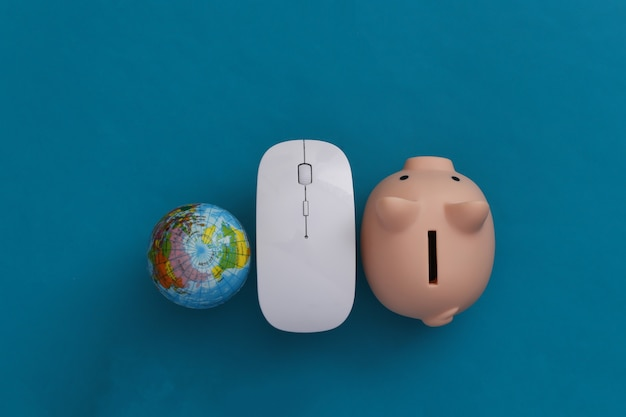 Global network. pc mouse and globe, piggy bank on blue background. online business, shopping. top view