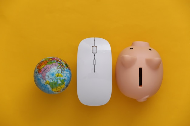Global network. pc mouse and globe, piggy bank on yellow background. online business, shopping. top view