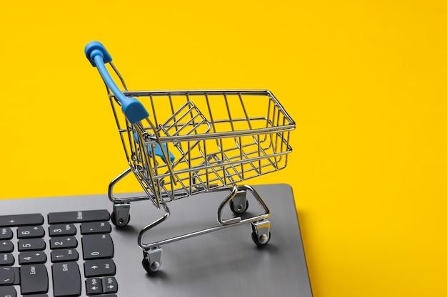 글로벌 온라인 슈퍼마켓. 노트북 키보드에 쇼핑 카트입니다.