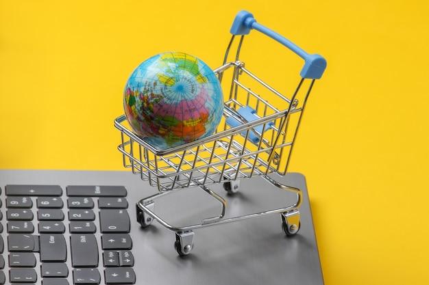 グローバルオンラインスーパーマーケット。ノートパソコンのキーボードで地球儀とショッピングトロリー