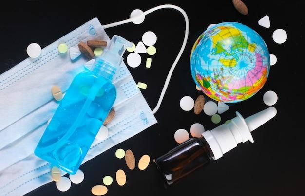 글로벌 유행성 코로나 19. 파란색 액체, 의료용 안면 마스크, 지구본, 알약, 비강 스프레이가 들어있는 방부제 병