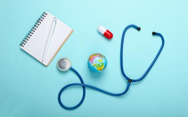 세계적인 유행병 정물. 글로브, 청진 기, 캡슐, 파란색 배경에 메모장. 평면도. 코로 노 바이러스 발생
