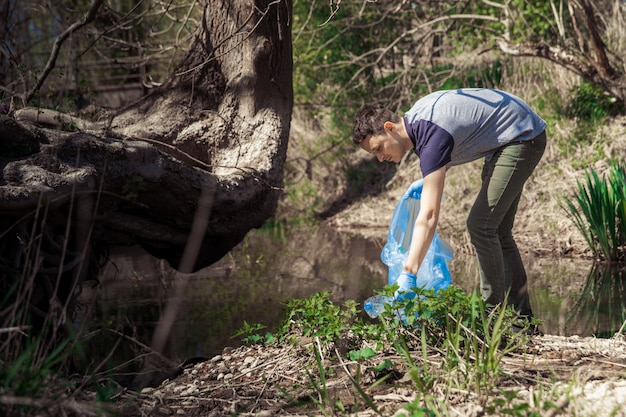 Global pollution of the planet with plastic waste. volunteers help ecology by clearing forests and meadows by collecting waste