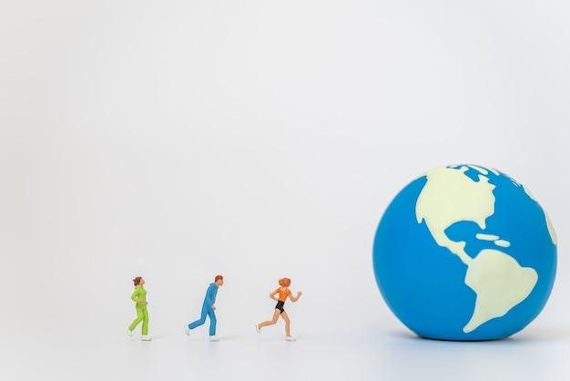 グローバルスポーツ健康の概念。ミニワールドボールに走るランナーミニチュアフィギュアの人々のグループ