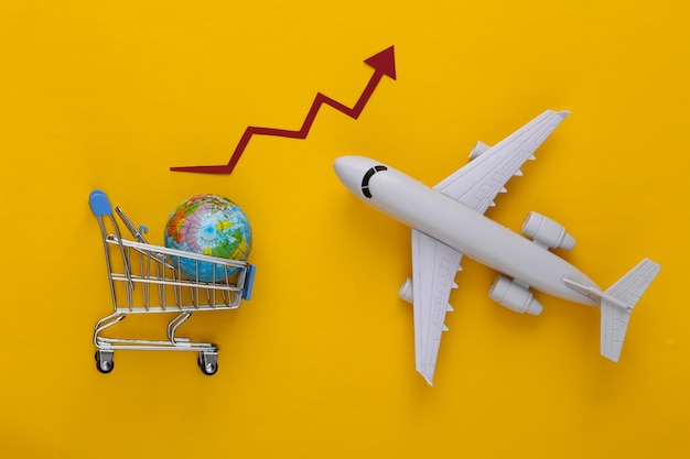 Global supermarket. increased international shipping. shopping trolley, globe and plane with growth arrow on yellow