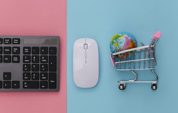 Global supermarket. pc keyboard and shopping trolley with globe on pink blue pastel