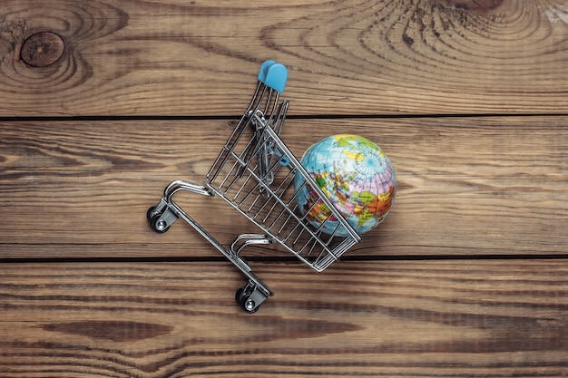 グローバルスーパーマーケット、配送。木製のテーブルの上の地球とショッピングトロリー