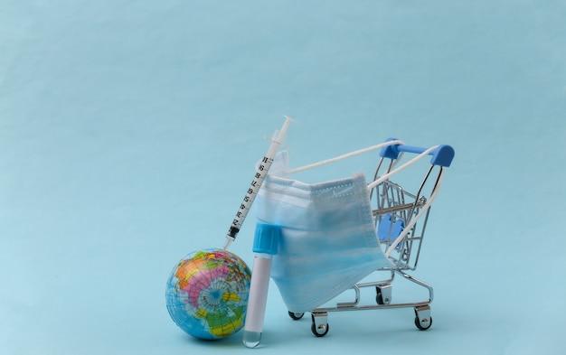 글로벌 백신 접종. 파란색 배경에 테스트 튜브, 주사기, 글로브가 있는 의료용 마스크 쇼핑 트롤리