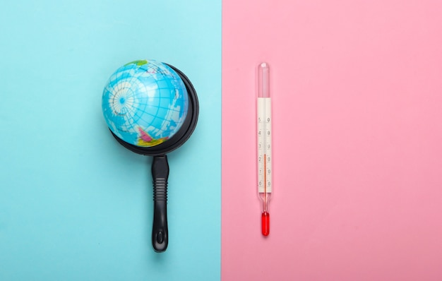 地球温暖化の概念。青ピンクのパステルカラーの壁におもちゃの鍋と温度計のミニグローブミニマリズム。私たちの時代の気候問題。上面図