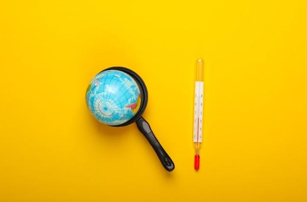 地球温暖化の概念。おもちゃの鍋のミニグローブと黄色い壁の温度計ミニマリズム。私たちの時代の気候問題。上面図