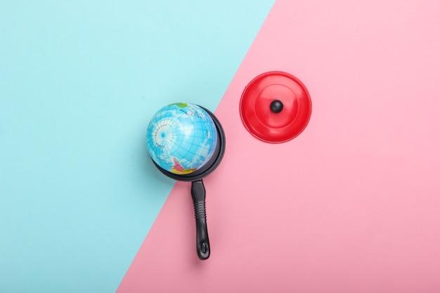 地球温暖化の概念。青ピンクのパステルカラーの壁におもちゃの鍋のミニ地球儀上面図。ミニマリズム。私たちの時代の気候問題。上面図