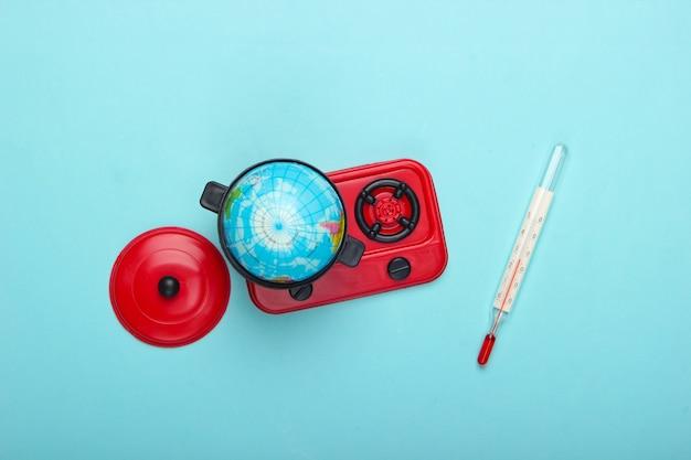地球温暖化の概念。ストーブと温度計のおもちゃの鍋にミニグローブ。青いパステルカラーの壁上面図。ミニマリズム。私たちの時代の気候問題。上面図