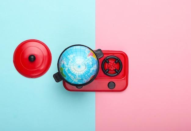 地球温暖化の概念。ストーブのおもちゃの鍋のミニ地球儀。青ピンクのパステルカラーの壁上面図。ミニマリズム。私たちの時代の気候問題。上面図