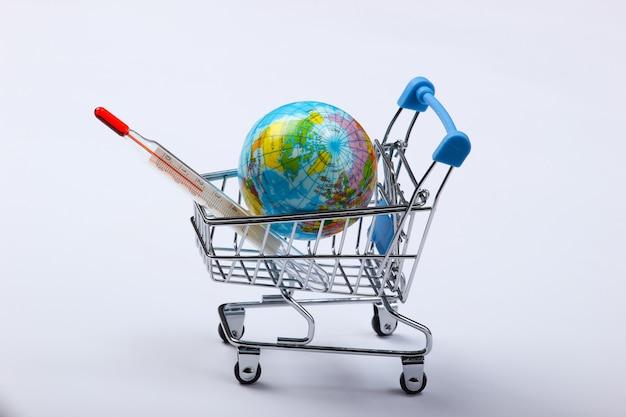 지구 온난화 개념. 글로브와 온도계는 흰색에 쇼핑 트롤리