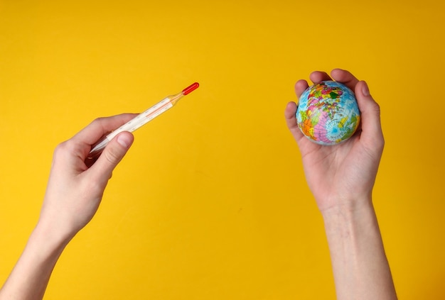 Global warming. female hands holding a thermometer and a globe on yellow background. top view