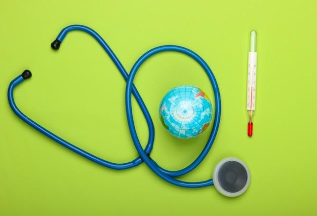 지구 온난화 정물. 글로브와 온도계, 녹색 벽에 청진 기 글로벌 기후 문제입니다. 지구 행성 치료. 에코 컨셉