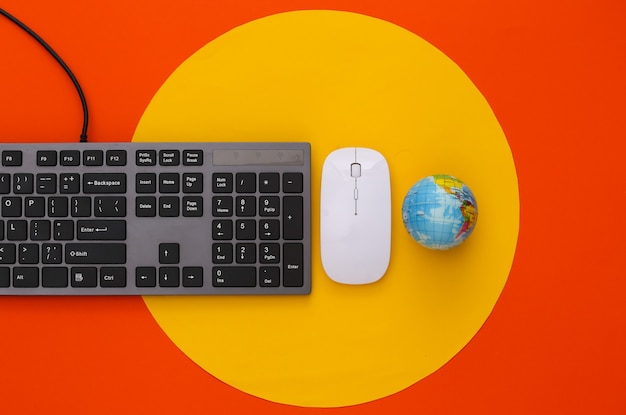 Global web. pc keyboard with pc mouse, globe on orange with yellow circle