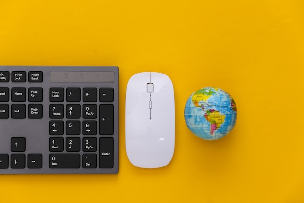 Global web. pc keyboard with pc mouse, globe on yellow