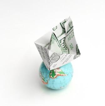 地球儀とドル紙幣から紙のボート。白い背景で隔離