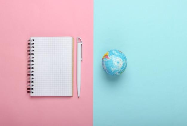 Глобус и блокнот на розовом голубом пастельном фоне. вид сверху. минимализм. концепция образования, география