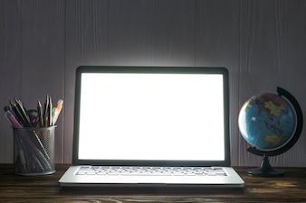 Globe and stationery near laptop
