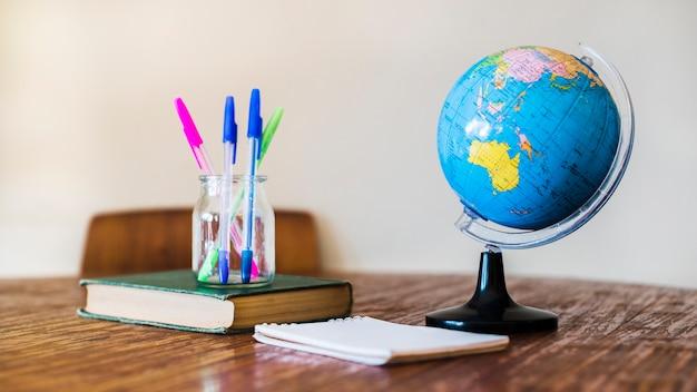 Глобус и канцелярские принадлежности на столе