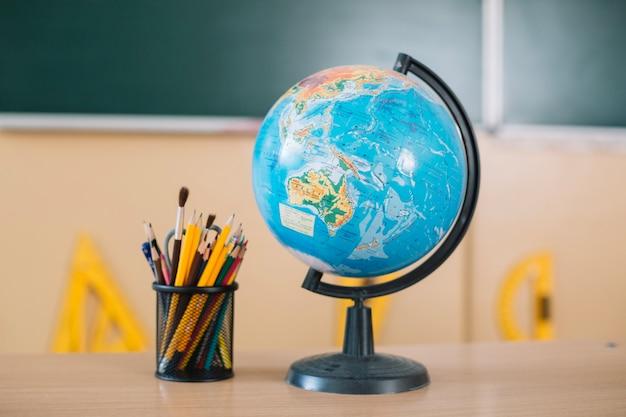 学校のテーブルの上のグローブと筆記具