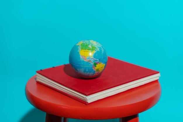 텍스트 복사 공간이 있는 화려한 파란색 배경의 의자에 있는 빨간색 책 위에 있는 글로브 공