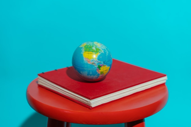 Globe ball in top of a red book in a stool with colorful blue background with copy space for text