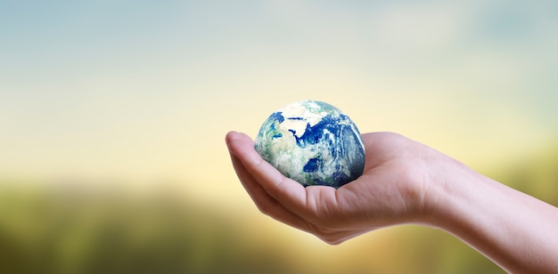Globe ,earth in  hand, holding our planet glowing.