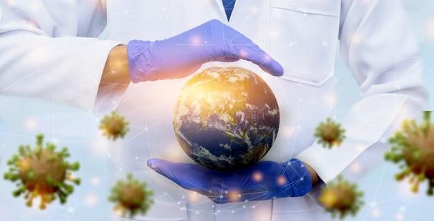 ウイルスバナーから保存する手袋を身に着けている医者の手で地球