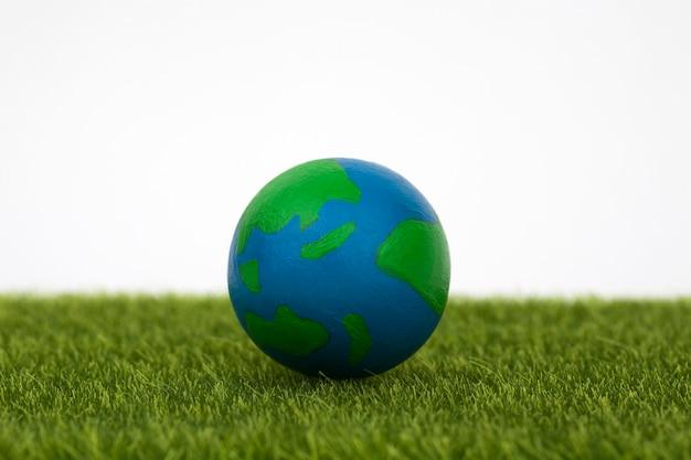 Globe on green grass on white