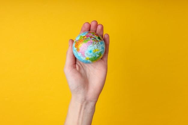 Глобус в женской ладони на желтой стене концепция ухода за планетой земля