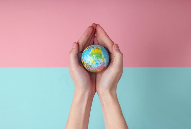 블루 핑크 파스텔 배경에 여성 손바닥에 글로브. 행성 지구 관리 개념