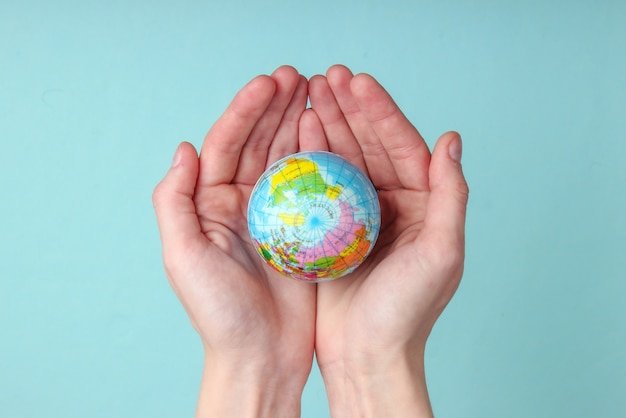Глобус в женских ладонях на синей стене концепция ухода за планетой земля